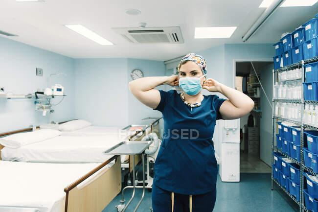 Врач в синей больничной форме стоит и готовится к операции в коридоре клиники, смотрит в камеру — стоковое фото