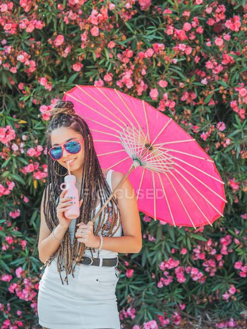 Sorridente sottile giovane donna in abito estivo e occhiali da sole con ombrello bere bevanda vicino alberi in fiore — Foto stock