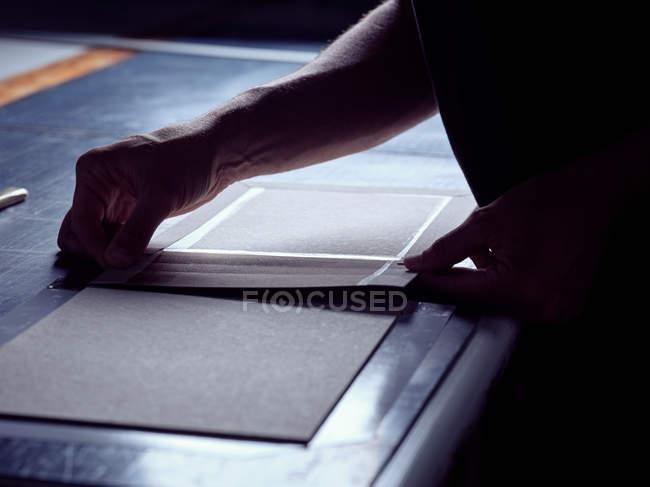 Руки человека, создающего книгу в твердом переплете склеивания ткани на коробке кусок работает за столом — стоковое фото