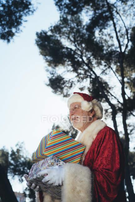 Веселий старший чоловік в костюмі Діда Мороза стояв з подарунками і дзвіночок в балакучих руках на фоні природи — стокове фото