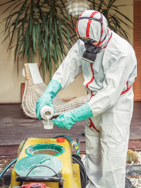 Man in suit for fumigation pouring chemical into tank — Stock Photo
