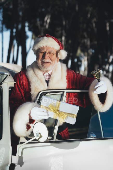 Усміхнений старший чоловік у костюмі Діда Мороза стояв у старому двері Ван з загорнуті подарунок і дзвін у сонячний день — стокове фото