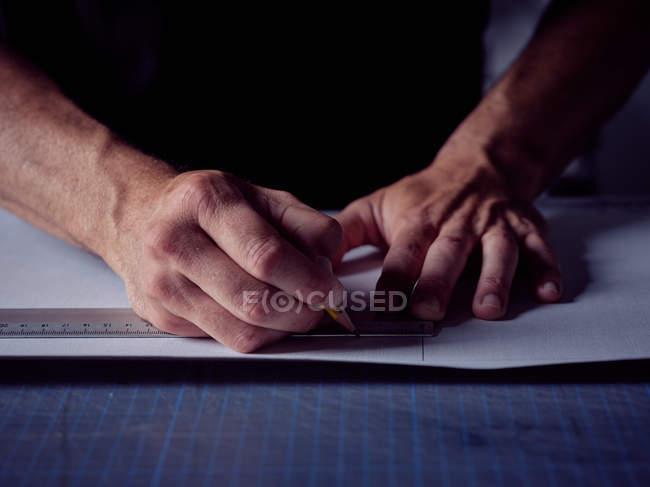 Mani di uomo che lavora in studio di bookmaking e misura copertina per libro con matita e righello — Foto stock