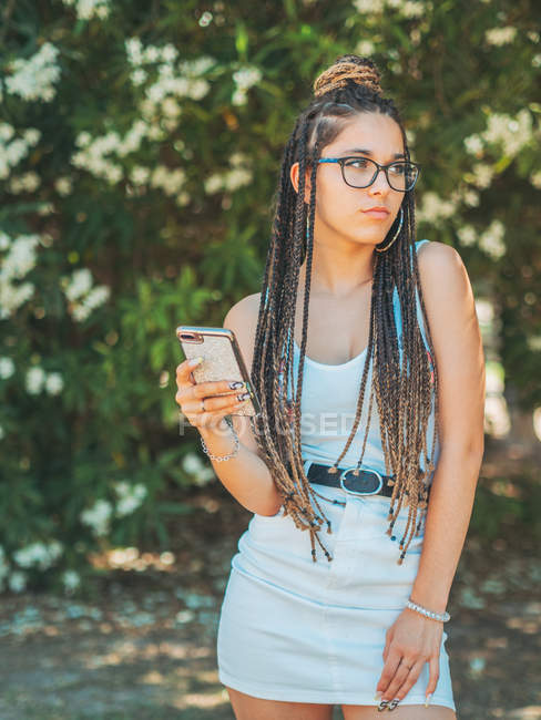 Stylish young woman wearing glasses and summer clothes using smartphone and looking away in park — Stock Photo