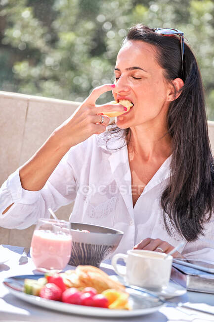 Woman sitting at table with served breakfast on open sunlit patio while eating a donut and laughing with eyes closed on blurred background — Stock Photo