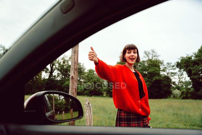 Приваблива стильна жінка жестами з великим пальцем, щоб зловити автомобіль на дорозі вздовж зеленої області — стокове фото