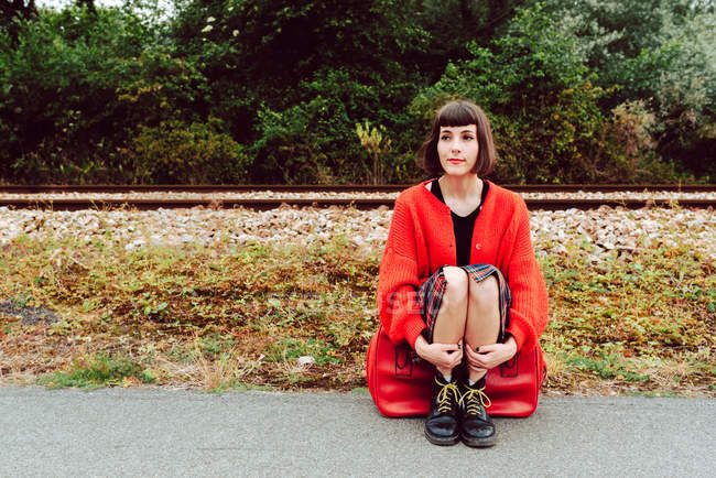 Thoughtful woman sitting on red suitcase on road near railroad ties — Stockfoto