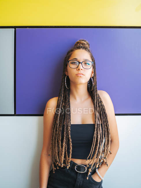 Stylish teenage girl with hand in pocket and unique braids looking at camera on colorful background — Photo de stock