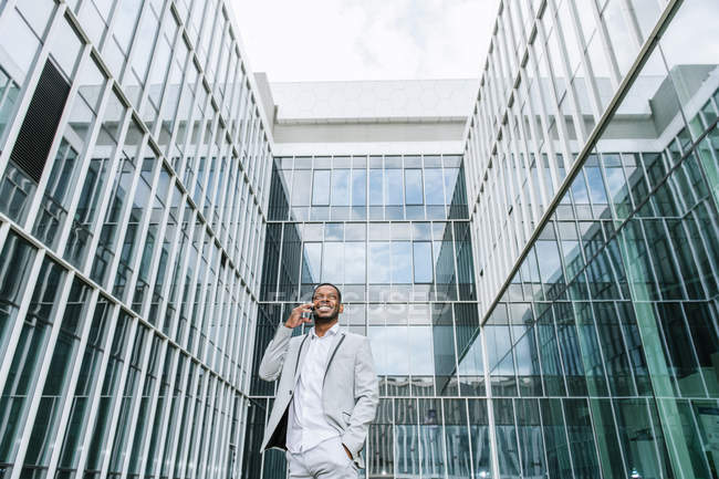 Elegant black man talking smartphone near building — Stock Photo