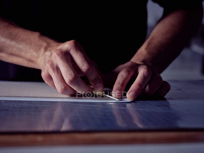 Руки человека, работающего в букмекерской мастерской, и измерительная крышка для книги карандашом и линейкой — стоковое фото