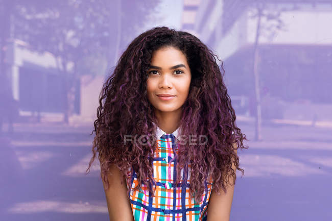 Portrait of charming young ethnic young woman with curly hair looking at camera against purple glass wall — Stock Photo