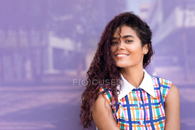 Portrait of happy young ethnic young woman with curly hair looking at camera against purple glass wall — Stock Photo