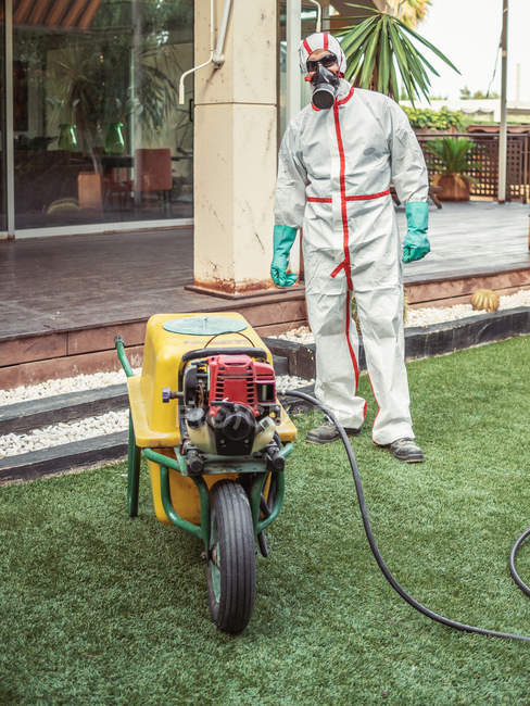 Specialist in uniform for fumigation holding yellow trolley in yard — Stockfoto