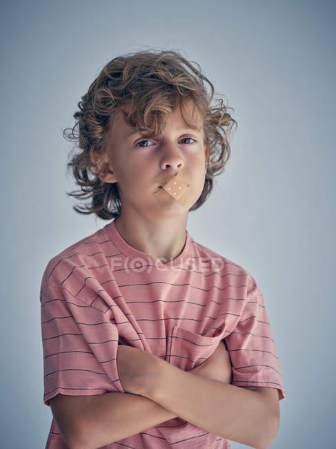 Lockiges, nachdenkliches Kind schweigt mit Gips auf dem Mund und blickt in die Kamera — Stockfoto