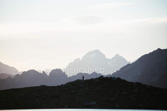 Величественный горный пейзаж с человеческим силуэтом — стоковое фото