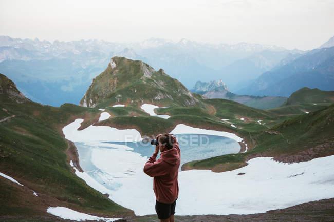 Homme photographiant un paysage de montagne — Photo de stock