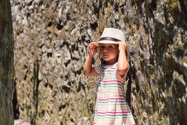 Actif adorable enfant en chapeau appuyé sur un mur pierreux dans la lumière du soleil et en regardant la caméra — Photo de stock