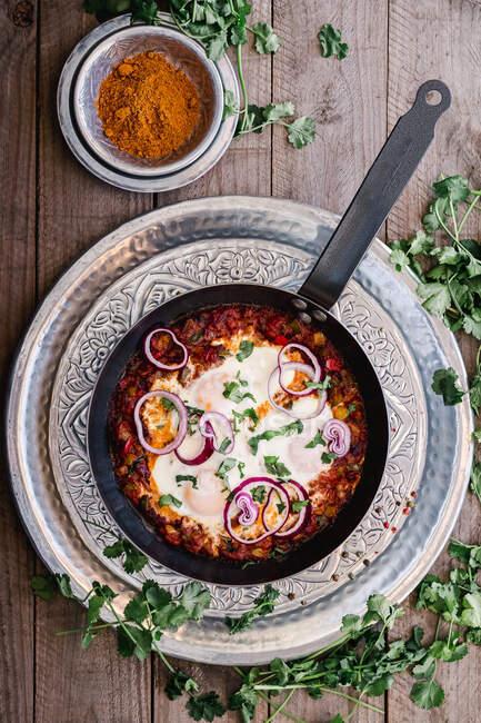Сверху вкусная ароматическая шакшука, украшенная луком и зеленью на сковороде на серебряной тарелке и куркума в миске на деревянном столе — стоковое фото