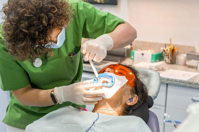 Стоматолог виробляє зуби, наповнені пацієнтом. — стокове фото