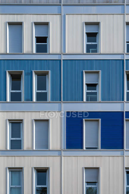 Екстер'єр сучасного барвистого міського будинку з довгою половиною розкритими вузькими вікнами — стокове фото