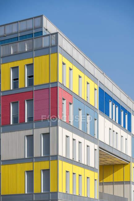 Esterno di casa urbana colorata contemporanea con lunghe finestre strette a metà aperte — Foto stock