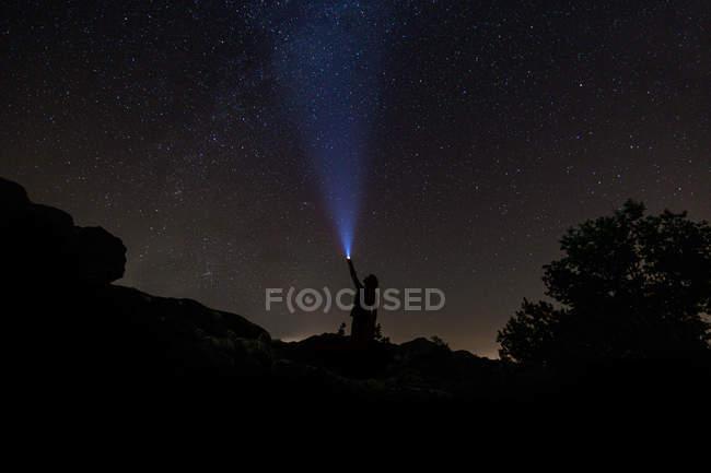 Night sky with silhouette of man lighting with flashlight — Stock Photo