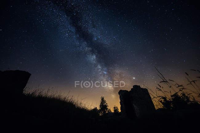 Cielo nocturno con la Vía Láctea y silueta de ruina - foto de stock