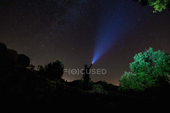Céu noturno com silhueta de homem iluminação com lanterna — Fotografia de Stock