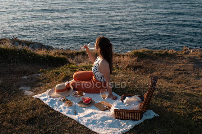 Side view of woman relaxing with drink on mat for picnic by serene water and hills — Stock Photo