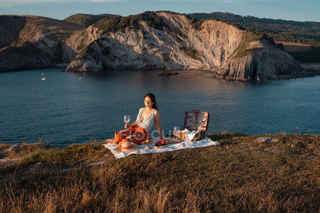 Young woman relaxing with drink on mat for picnic by serene water and hills — Stock Photo