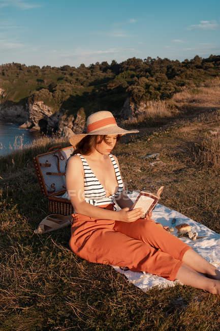 Женщина в шляпе читает книгу сидя на коврике для пикника под солнцем — стоковое фото