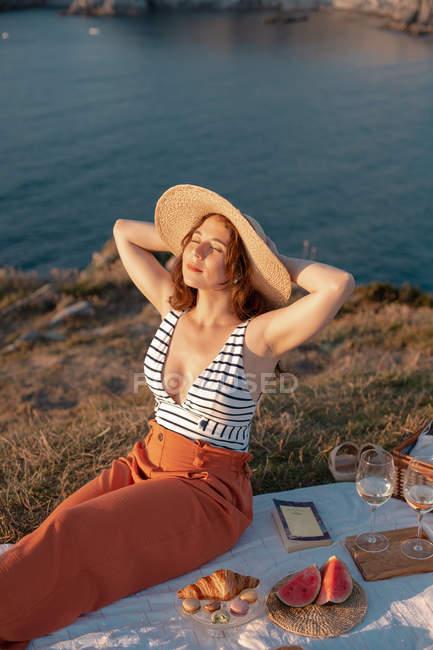 Женщина в соломенной шляпе наслаждается сидением на белом пикнике рядом с корзиной на газоне с закрытыми глазами — стоковое фото