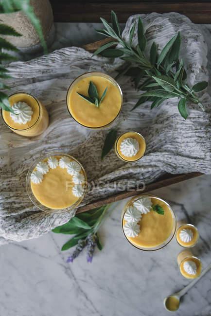 Sabroso mousse de mango aromático en vasos decorados con hojas sobre mantel - foto de stock
