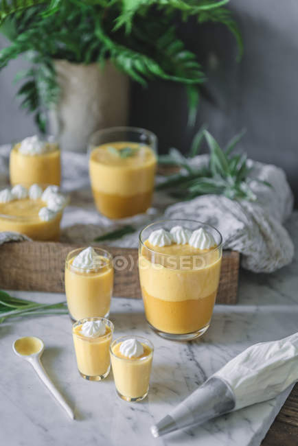 Tasty aromatic mango mousse in glasses on white marble surface — Stockfoto