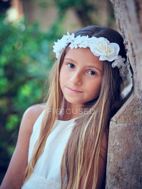 Portrait of little pretty girl wearing white dress flower headband leaning on wall and looking at camera — Stock Photo