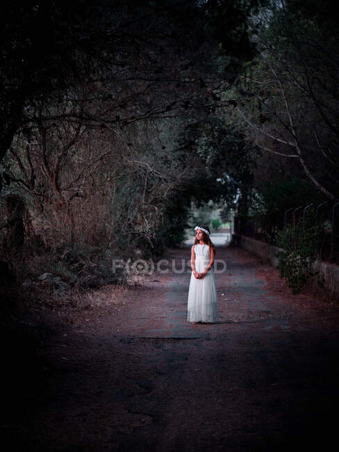 Little lonely girl in long white dress standing on road in dark alley looking away — Stock Photo