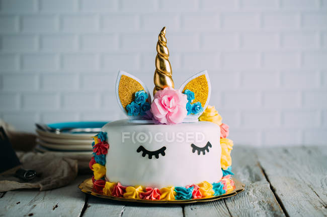 Cute unicorn cake with painted closed eyes on wooden table — Stock Photo