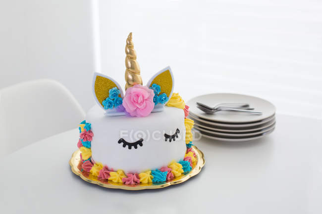 Cute unicorn cake with painted closed eyes on white table — Stock Photo