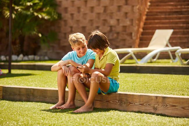 Веселі хлопці дивляться смартфон сидячи на городі. — стокове фото