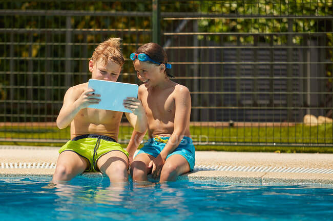 Boys on poolside browsing tablet — Stock Photo
