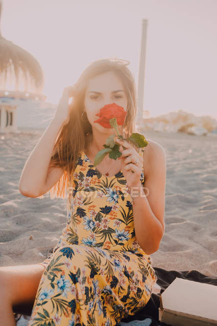 Charming thoughtful woman with rose in hand sitting and looking in camera alone in sunlight on seaside — Stock Photo