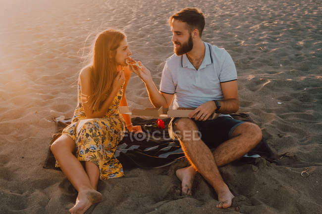 Bearded amorous man and long-haired woman feeding each other with tenderness in sunlight — Stock Photo