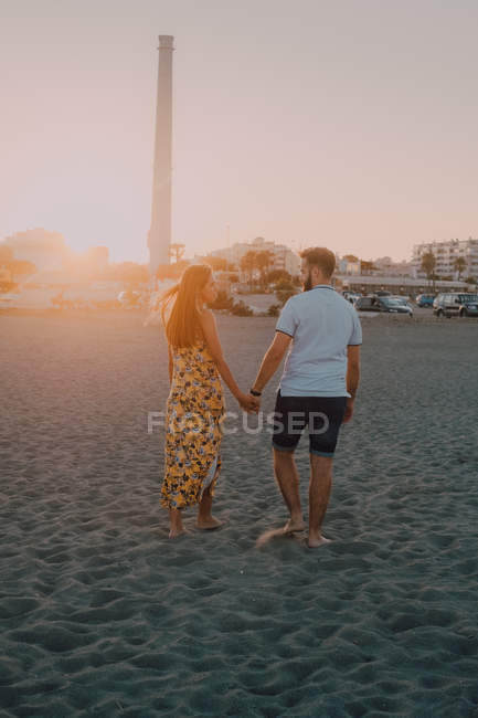 Happy young people in love walking looking to each other and holding hands barefoot in seaside in sunlight — Stock Photo