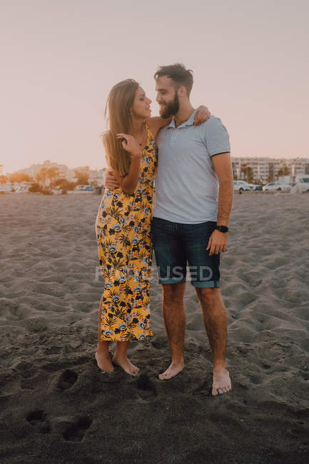 Happy young people in love standing looking to each other and embracing barefoot in seaside in sunlight — Stock Photo