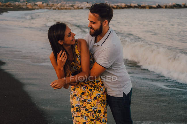 Амурних людина обіймає чарівну жінку ніжно на березі моря — стокове фото