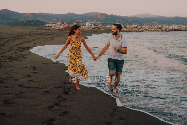 Happy young people in love running looking to each other and holding hands barefoot in seaside in sunlight — Stock Photo