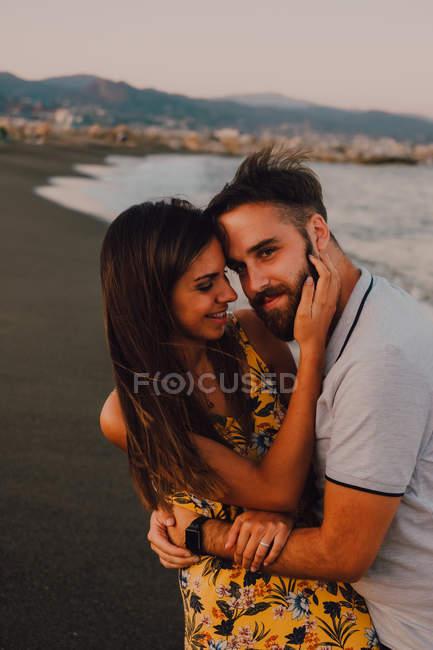 Амурный мужчина обнимает женщину нежно касаясь лица на берегу моря — стоковое фото