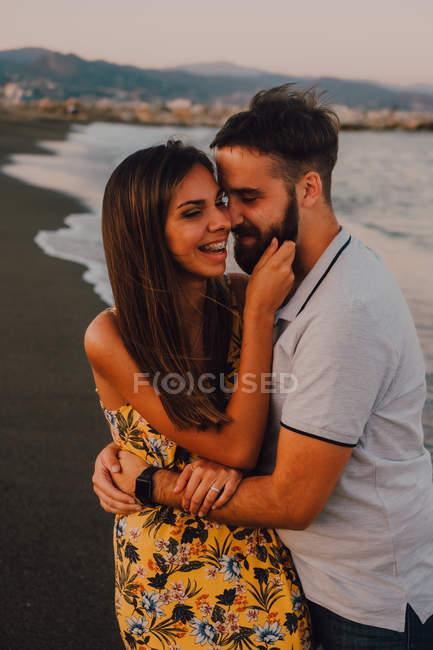 Amorous man hugging woman gently touching face at seaside — Stock Photo