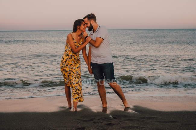 Amorous man hugging charming woman gently at seaside — Stock Photo