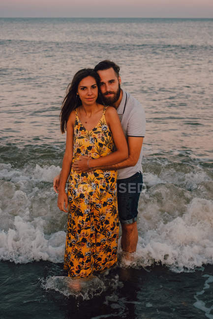 Любовна людина обійматися жінку і дивлячись в камеру м'яко на березі моря — стокове фото